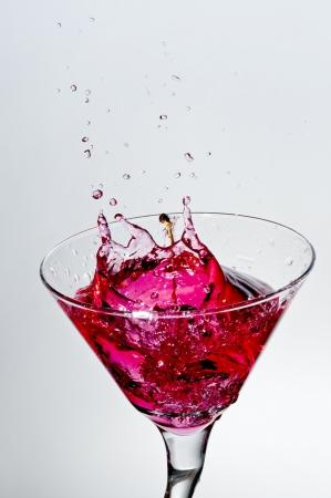 Cherry splash on glass of red Martini photo