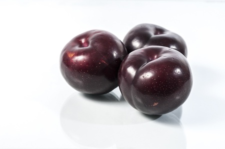 three red delicious ripe plums ready to eat photo