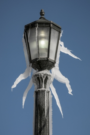 Lamp post covered with icycle during winter time photo