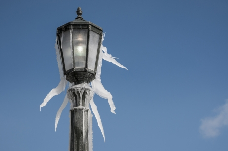 Lamp post covered with icycle during winter time Stock Photo