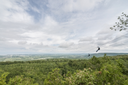 longshot: couple zip lining over the tree canopy
