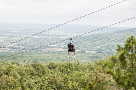 longshot: Man zip lining over the tree canopy