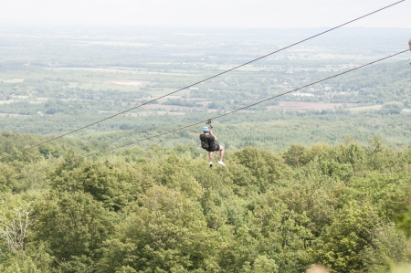 longshot: Man zip lining over the tree canopy