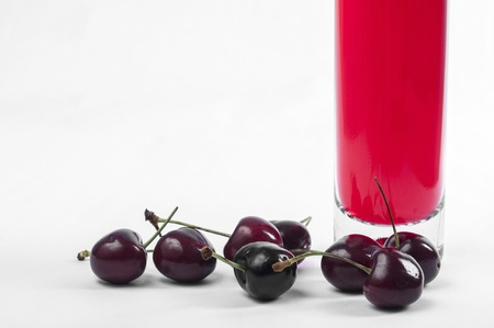 Red cherry and wine bottle close up photo