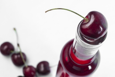 Red cherry on top of wine bottle photo