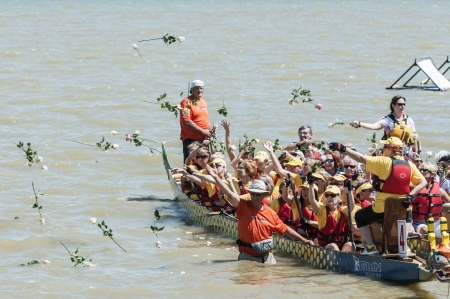 dragonboat: dragon boat people throwing rose on the river Editorial