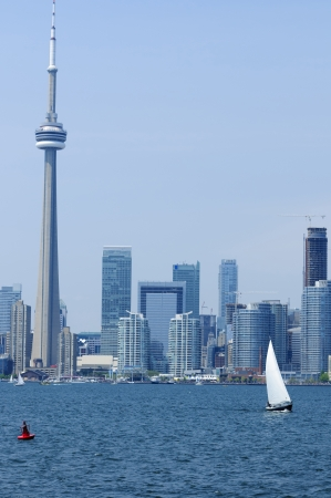 Small boat sailing at Toronto harbor with high rise building in the back ground