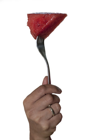 Slice of watermelon on a tip of a fork held by a hand photo