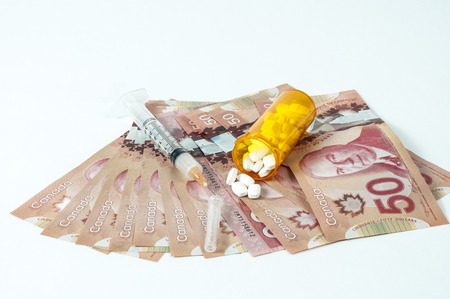 doctor money: Canadian dollar bill with syringe and pills
