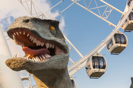 Statue of a dinosaur head with ferris wheel on the background