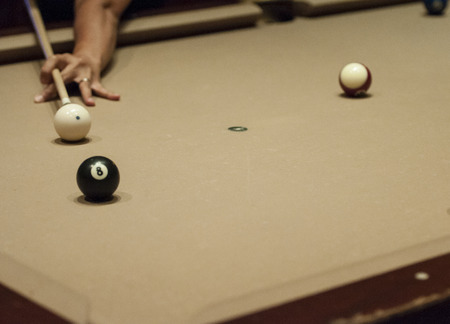 player aiming for the shot by a White cue ball and 8 ball