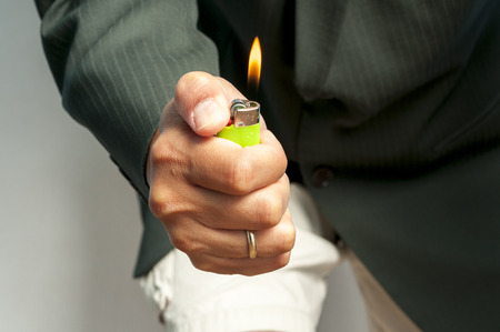 Man on suit handing a cigarete lighter flame Stock Photo