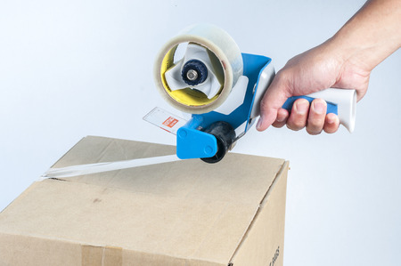 sellotape: Hand holding a packaging tape sealing a box