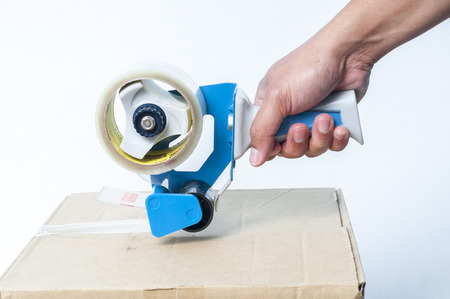 sealing tape: Hand sealing a box with packaging tape Stock Photo