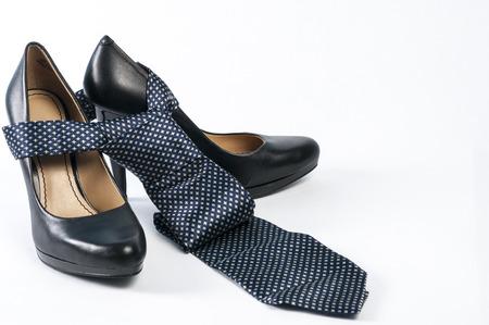 Black high heel shoe with neck tie over it Imagens
