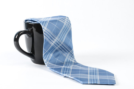 office stapler: A blue tie and a black coffee mug Stock Photo