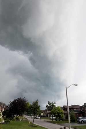 passing over: Storm cloud passing over residential area