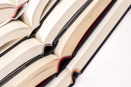 Open hard bound books stash on top of each other Stock Photo