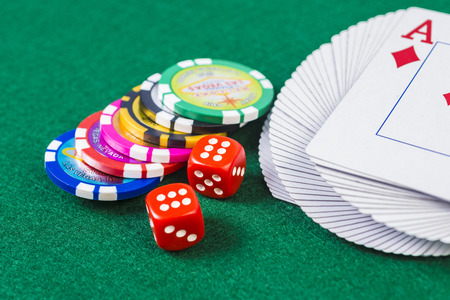 Twisted playing cards, dice and poker chip on top of felt surface Stock fotó - 37683477