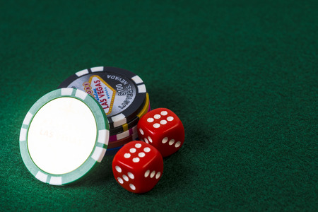 A pair of dice and poker chip on top of felt surface