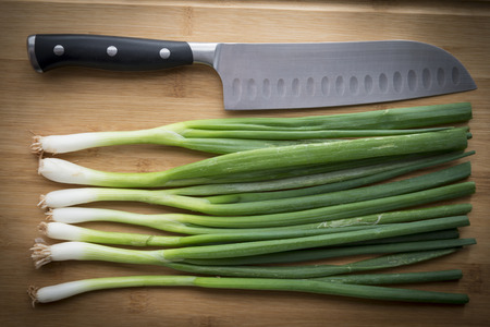 Spring onion , knife on top of wooden chopping board