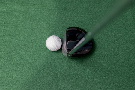 selectivity: Golf club and ball on a smooth green back ground