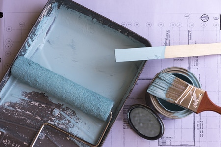 roller brush: Roller brush , paint brush and accessories with paper below.
