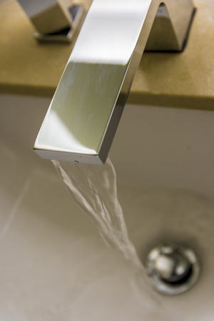 drinkable: Water coming out of a stainless steel water faucet. Stock Photo