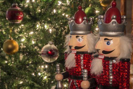 nut cracker: A pairof nut cracker with decorated Christmas tree in the background