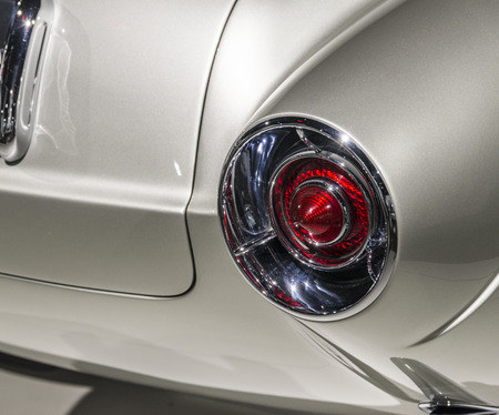 tail light: Silver bodied car with red tail light