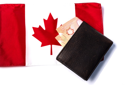 signifies: Wallet with cash on top of canadian flag,signifies Canadian economy Stock Photo