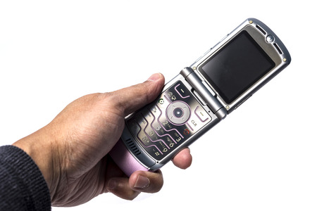 flip phone: Old classic flip phone held by a human hand
