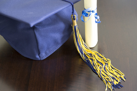 茶色の背景に圧延の卒業証書と卒業の帽子。 写真素材