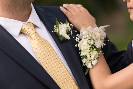 A prom couple showing showing both corsage.