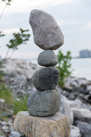 equipoise: Four rocks balance and stack on top of the others
