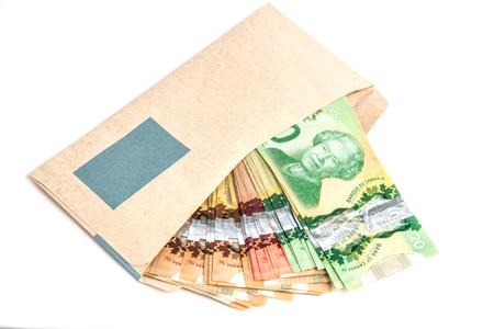 Canadian dollar bills inside a brown envelop.