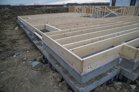 housebuilding: Wood floor joist on top of basement foundation wall.