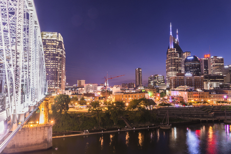 Nashville skyline at night with pedestrian bridge on the side.