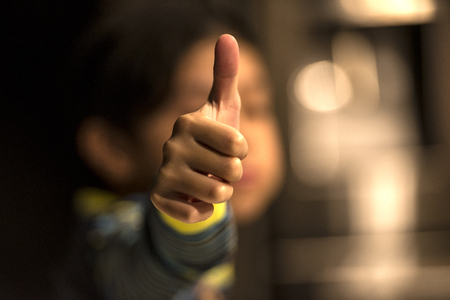 Thumbs up by a kid with blurred back ground.