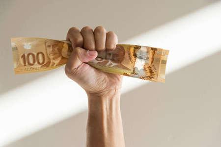 Hand tight fist squeezing canadian dollar bills.