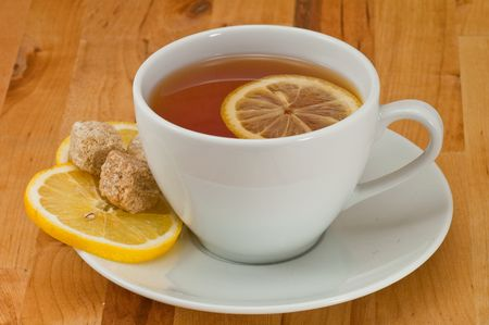 White porcelain cap of tea with sliced lemon and brown sugar on the wooden table photo