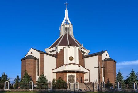 The modern Catholic church built of red brick.