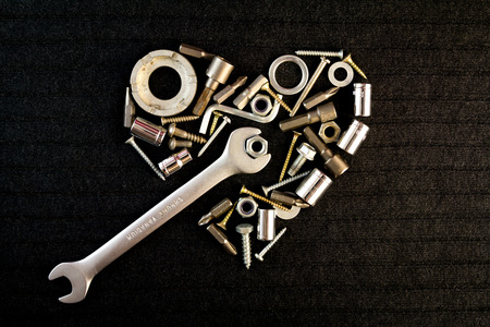 heart of theart of the tools and screw nuts on a dark gray background Banco de Imagens