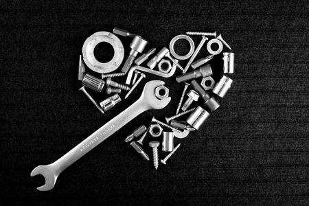 ツールと黒と白の暗い灰色の背景上のねじナットのアートの中心