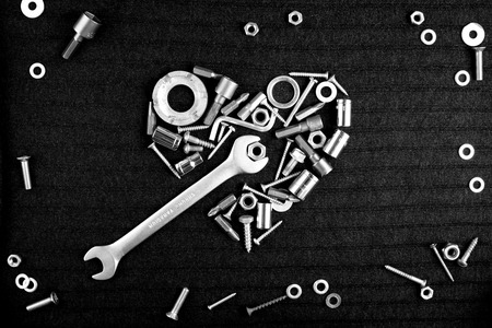 heart of theart of the tools and screw nuts on a dark gray background in black and white photo