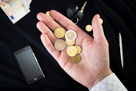 coins on the mans palm on a black background Banco de Imagens