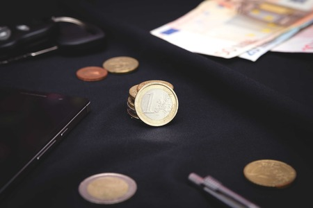 euro coins on a black background surrounded by content of the pockets