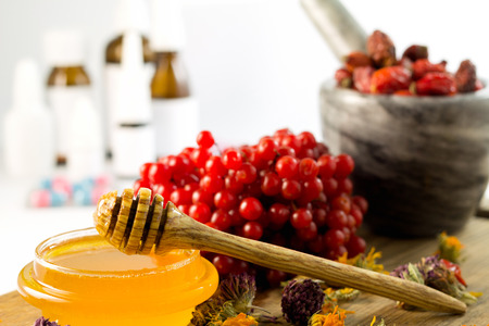 plant medicine: honey, herbs and medicines and pills in the background Stock Photo
