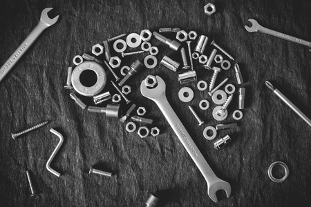 physiology: brain composed of the tools and screw on a dark gray background Stock Photo
