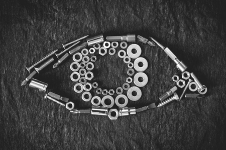 vision repair: human eye composed of the tools and screw on a dark background Stock Photo